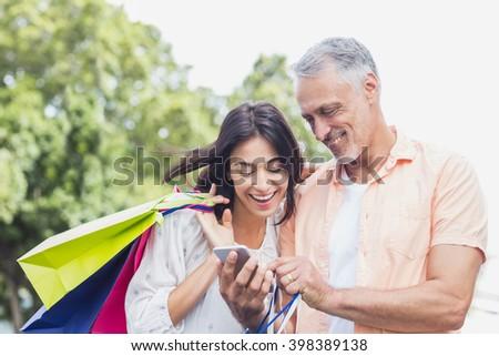 Happy couple using phone in city - stock photo