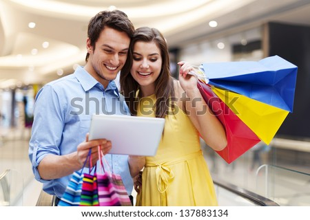 Happy couple using s digital tablet in the shopping mall - stock photo