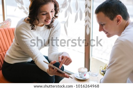 Happy couple using tablet in cafe