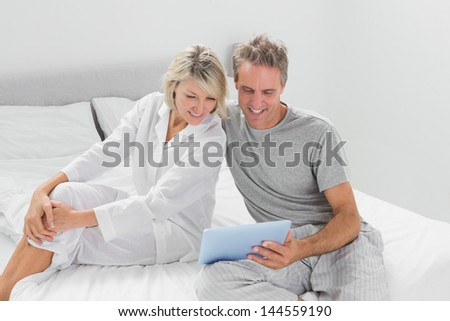 Happy couple using their digital tablet at home in bedroom - stock photo
