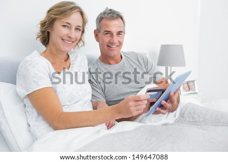Happy couple using their tablet pc to buy online looking at camera at home in bedroom - stock photo