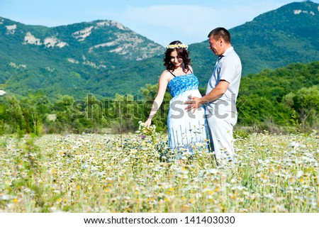 happy couple waiting baby in sunny day on chamomile field