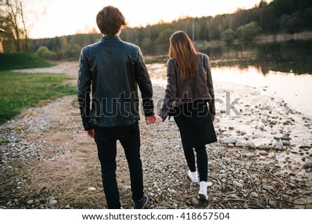 Happy couple walking and holding hands on the lake in summer evening. love concept - stock photo