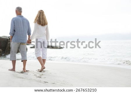 Happy couple walking by the sea at the beach - stock photo
