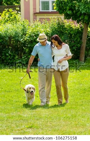 Happy couple walking golden retriever dog on park lawn smiling - stock photo