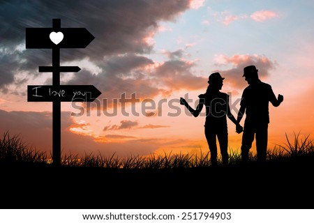 Happy couple walking holding hands against sun set