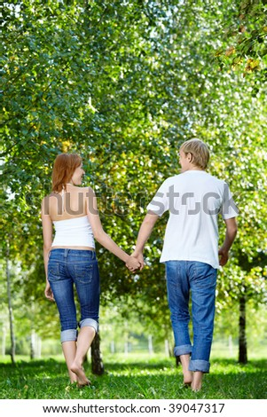 Happy couple walking in a summer garden - stock photo