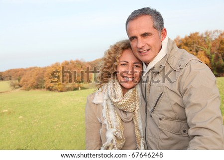 Happy couple walking in country field in autumn - stock photo