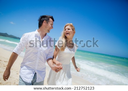 Happy Couple Walking On Beach.