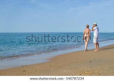 Happy couple walking on beach, male talking using mobile phone. Natural outdoors background. Back view image