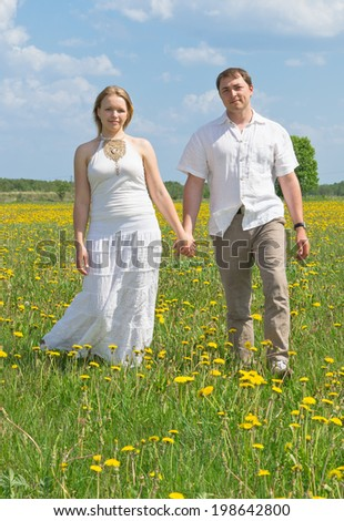 Happy couple walking on meadow on sunny day.