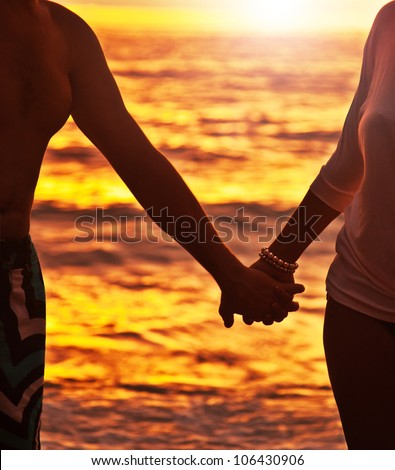 Happy couple walking on the beach, holding hands, close-up on silhouette, woman and man body over sunset background, romantic honeymoon travel, family enjoying vacation, life and nature, love concept