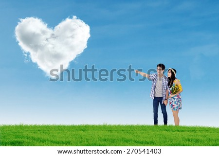 Happy couple walking on the meadow while holding hands and looking at cloud shaped a heart