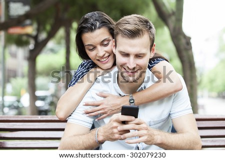 Happy couple watching a smart phone sitting on a bench in a park - stock photo