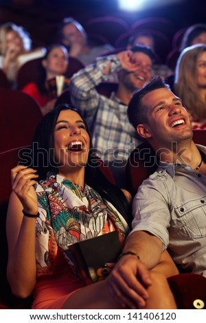 Happy couple watching comedy in movie theater, laughing. - stock photo