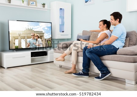 Happy Couple Watching Movie On Television Together While Sitting On Sofa At Home