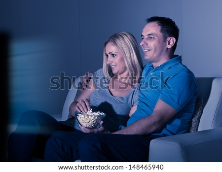 Happy Couple Watching Television And Eating Popcorn At Home - stock photo