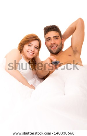 Happy couple watching television in bed - stock photo