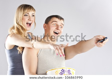 Happy couple watching television ,smiling. - stock photo