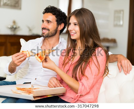 Happy couple watching television while eating pizza. Shallow depth of field, focus on the woman - stock photo