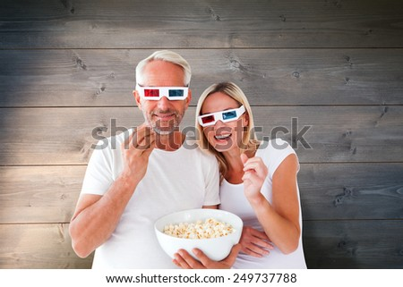 Happy couple wearing 3d glasses eating popcorn against bleached wooden planks background - stock photo