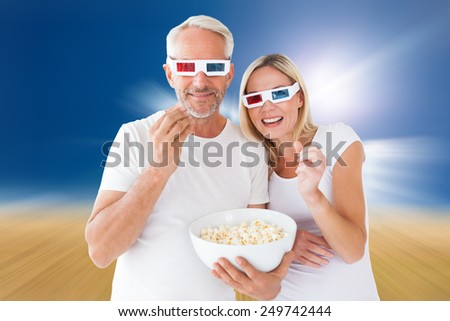 Happy couple wearing 3d glasses eating popcorn against sunny brown landscape - stock photo