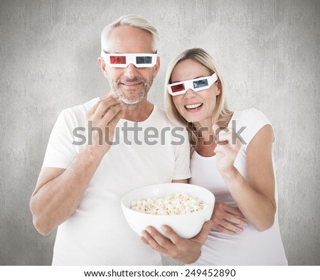 Happy couple wearing 3d glasses eating popcorn against weathered surface - stock photo