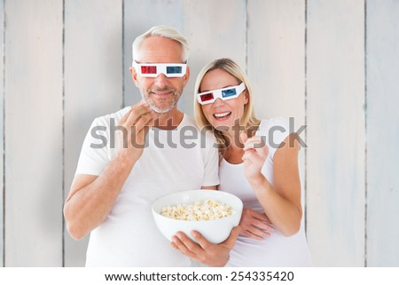 Happy couple wearing 3d glasses eating popcorn against wooden planks - stock photo