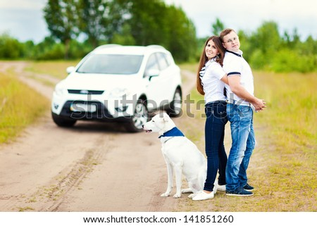Happy couple with a dog having fun outdoors outside the city - stock photo