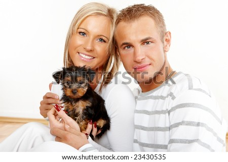 Happy couple with a funny puppy of Yorkshire Terrier