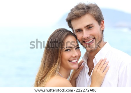 Happy couple with a white smile looking at camera on holidays on the beach isolated on white above - stock photo