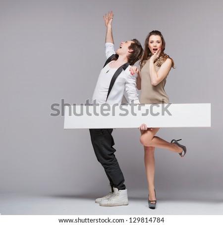 Happy couple with advert - stock photo