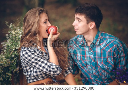 Happy couple with an apple outdoor - stock photo