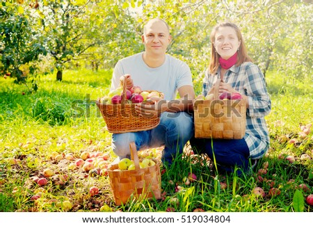 Happy couple with apples harvest in garden