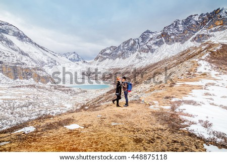 Happy couple with backpacks making a romance shot of themselves on top of a mountain - stock photo