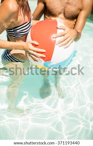 Happy couple with beach ball in the pool - stock photo
