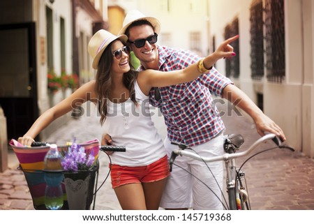 Happy couple with bikes in the city - stock photo