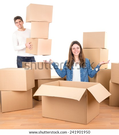 Happy couple with boxes moving into new home apartment  - stock photo