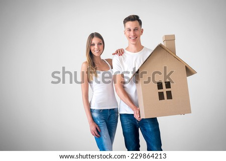 Happy couple with cardboard house