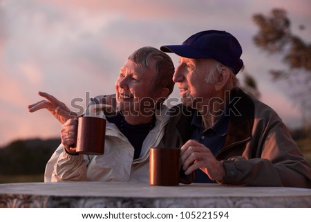Happy couple with coffee mugs in cool weather - stock photo