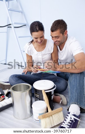 Happy couple with color samples to paint new house - stock photo