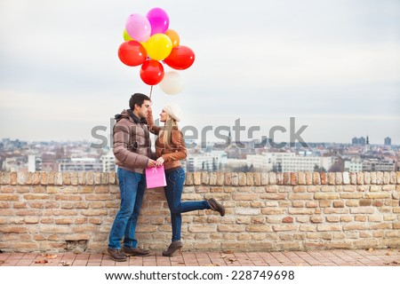 Happy couple with colorful balloons outdoors - stock photo