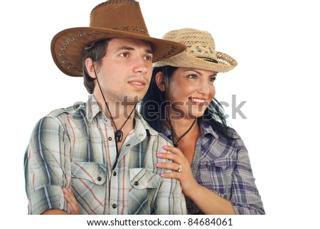 Happy couple with cowboy hats looking to the future isolated on white background