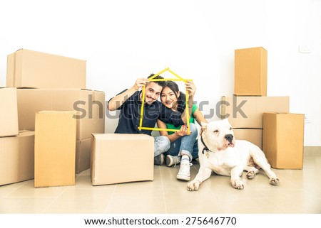 Happy couple with dog moving to a new home - Cheerful family starting a new life - Multi ethnic couple of lovers buy new apartment - stock photo