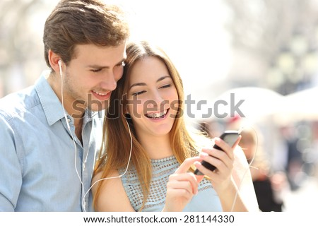 Happy couple with earphones sharing music from a smart phone on the street - stock photo