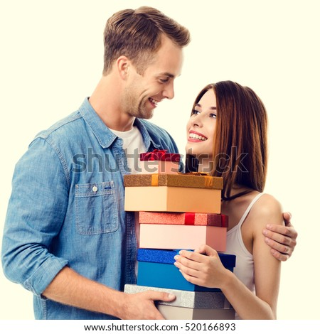 Happy couple with gift boxes, close to each other, with smile. Caucasian models in love, relationship, dating, flirting, lovers, romantic concept.