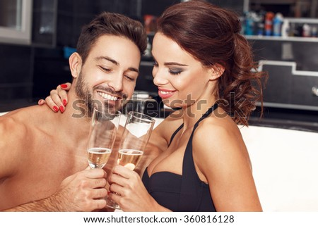 Happy couple with glasses of champagne in jacuzzi, honeymoon