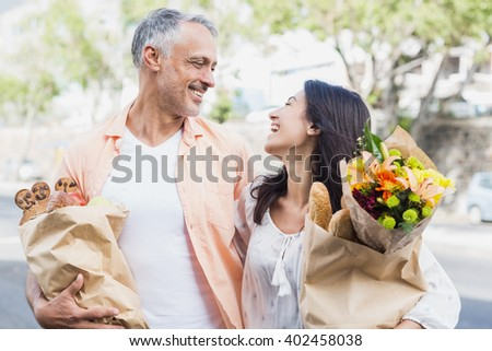 Happy couple with grocery bags standing in city - stock photo
