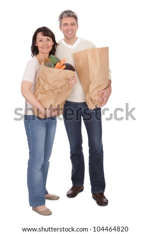 Happy couple with grocery shopping bags. Isolated on white - stock photo