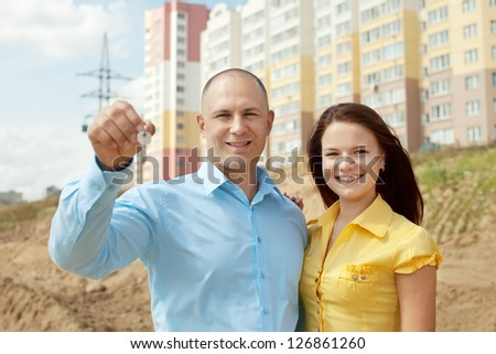 Happy couple with key against building new brick house - stock photo